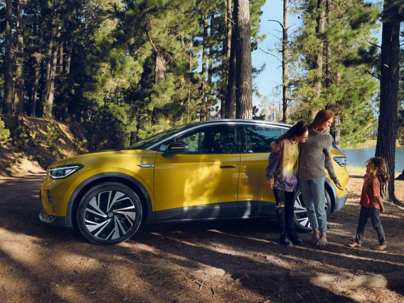 En kvinne og et barn står ved siden av VW Volkswagen ID.4