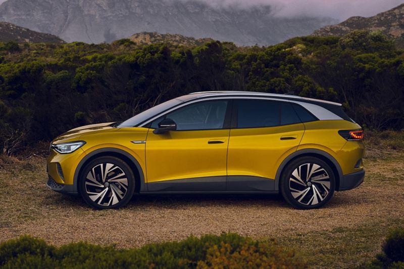 Vista laterale di Volkswagen ID.4 parcheggiata, con sullo sfondo montagne al tramonto