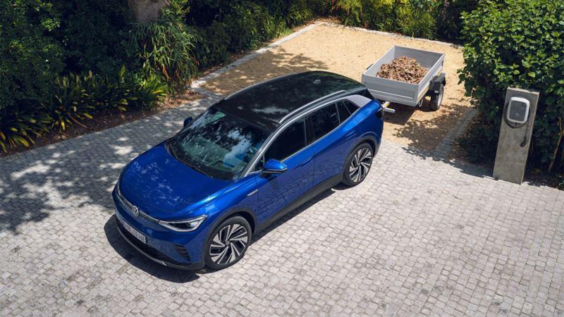 VW Volkswagen ID.4 elbil SUV parkert ved siden av en ladestasjon med tilhenger