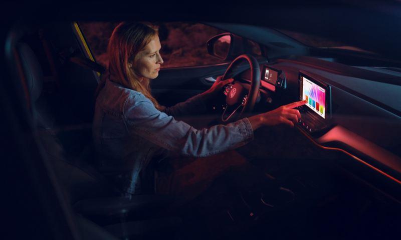 En kvinne velger ambientebelysning i kupeen i VW Volkswagen ID.4 elbil SUV