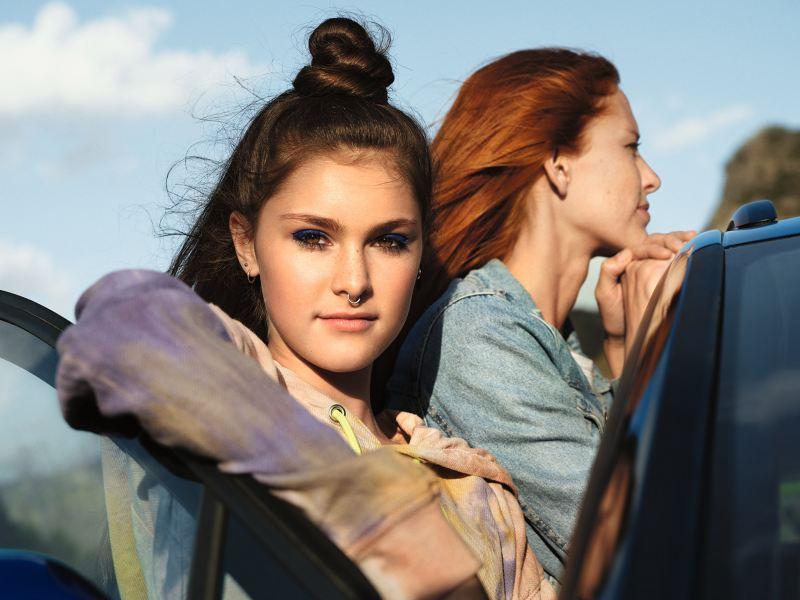 VW ID. 4 in blau, 2 Frauen stehen am Fahrzeug
