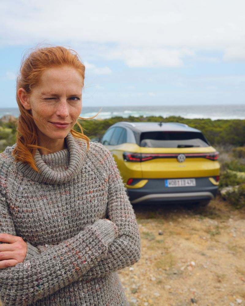 VW ID.4 Frau steht vor Heck des ID.4