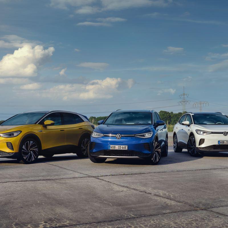 Drei VW ID.4 in gelb, blau und weiß stehen auf einem Hof im Grünen