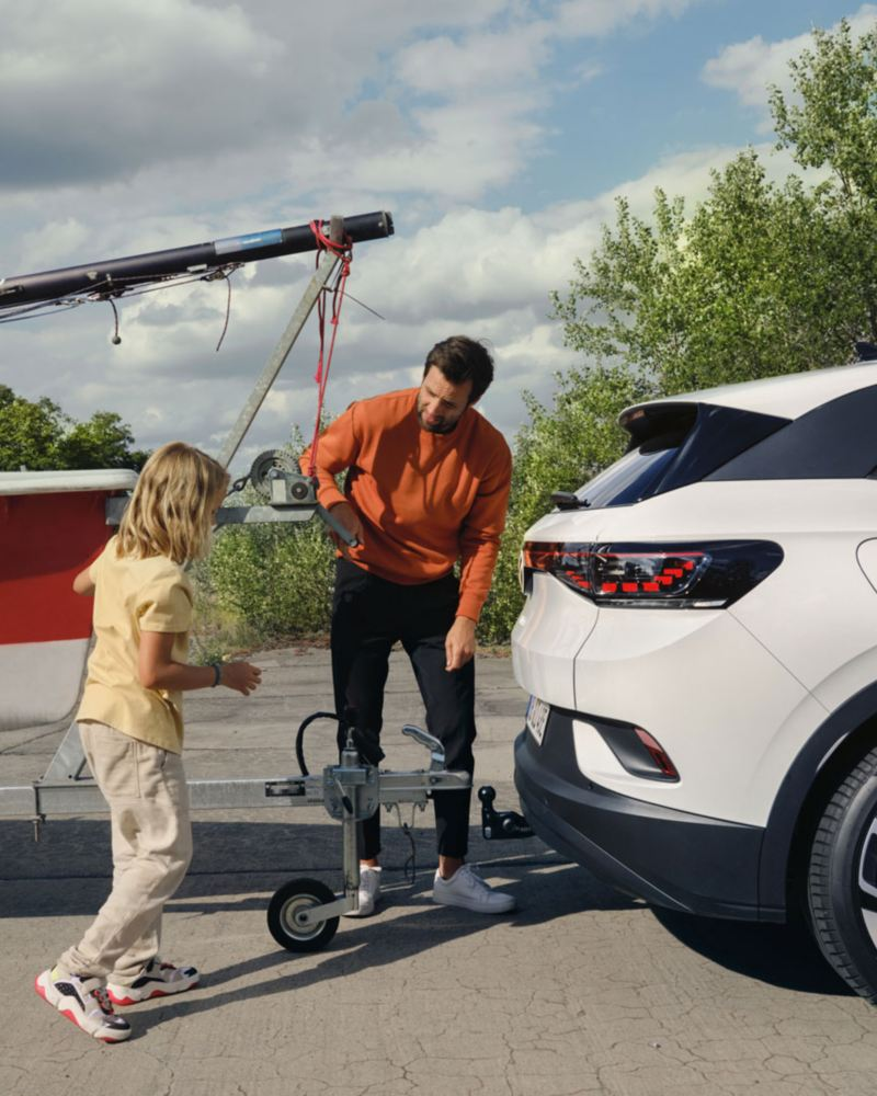 En mann kobler til tilhengeren på VW Volkswagen ID.4 elbil SUV