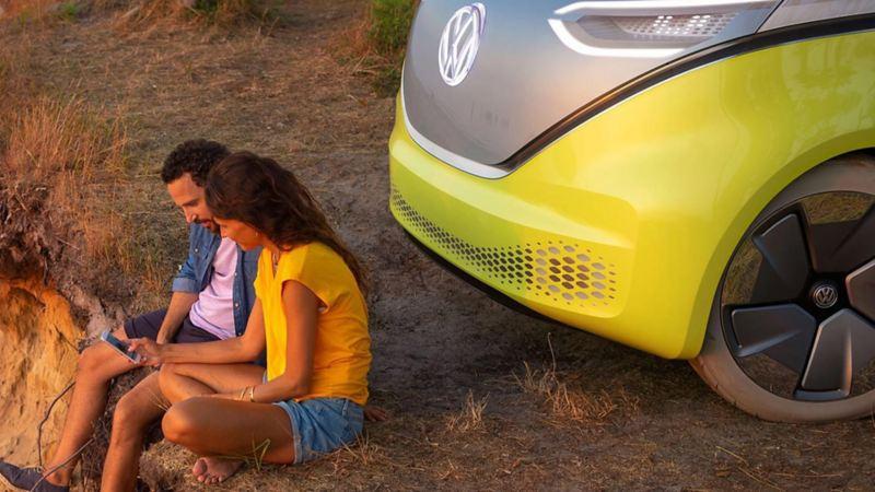 Una coppia di ragazzi seduti vicino ad una Volkswagen elettrica.