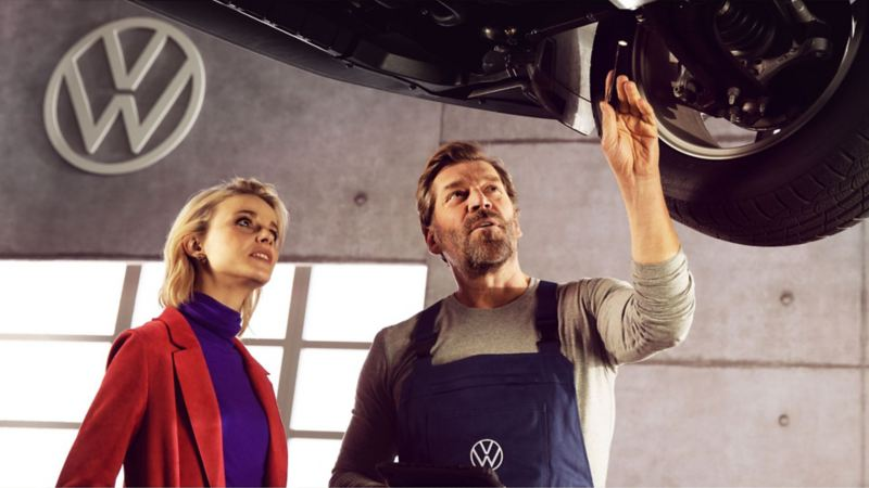 A woman and a man look at the underbody during the repair.