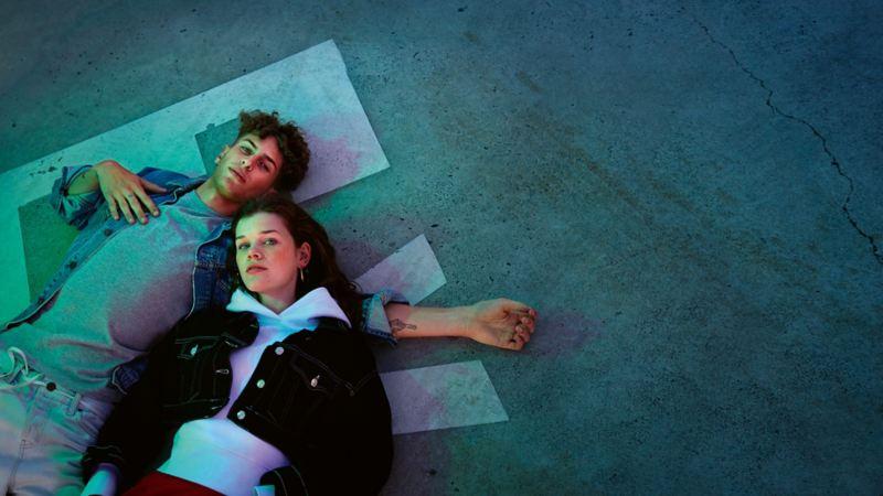 Par ligger på marken och håller om varandra