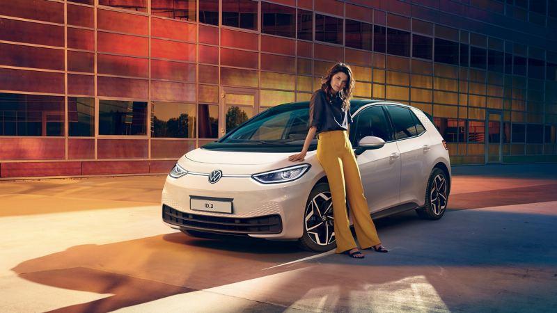 Donna appoggiata a VW ID.3 auto elettrica