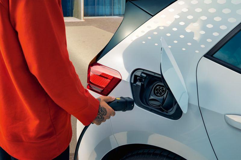 Uomo avvicina connettore alla presa laterale posteriore della Volkswagen elettrica per ricaricarla