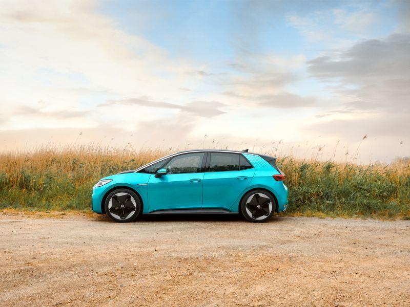 VW ID.3 in Makena-Türkis vor einem Feld, seitliche Ansicht, abgedunkelte Heckscheiben, Felgen Sanya 20 Zoll