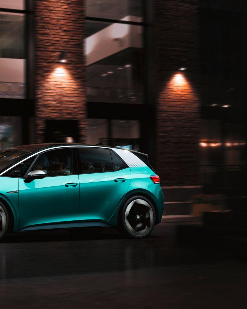 vista laterale Volkswagen ID3 1ST azzurra in movimento in città di notte