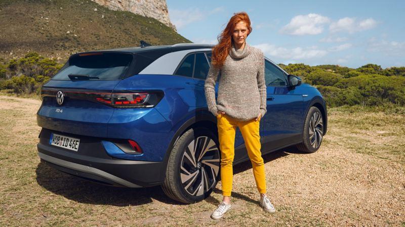 A woman standing near Volkswagen ID.4