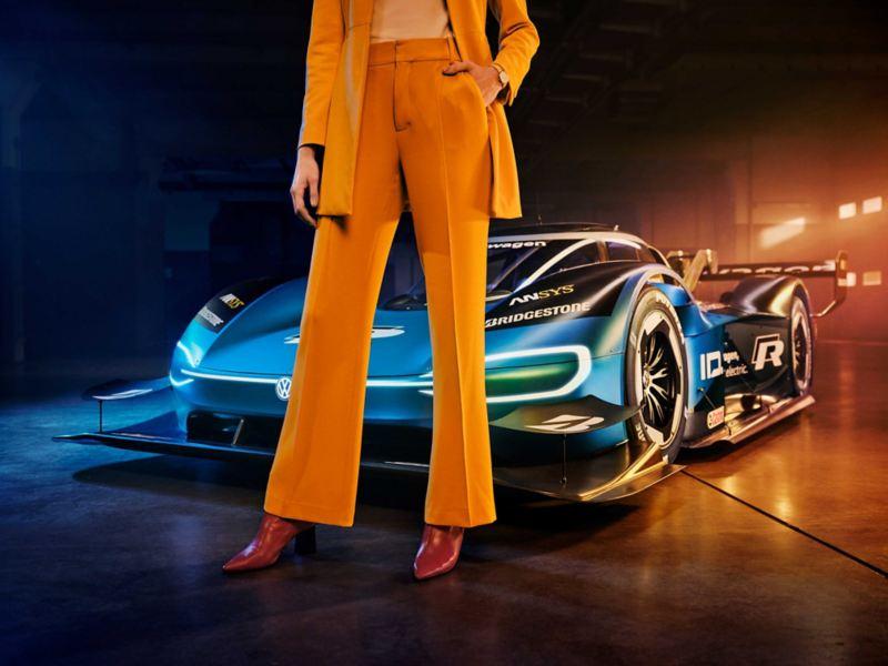 Kvinnelig modell i buksedrakt foran Volkswagen ID.R, eldrevet racerbil, lagerhall