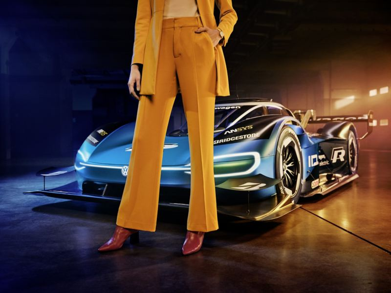 female model in pantsuit in front of the Volkswagen ID.R electric race car, warehouse