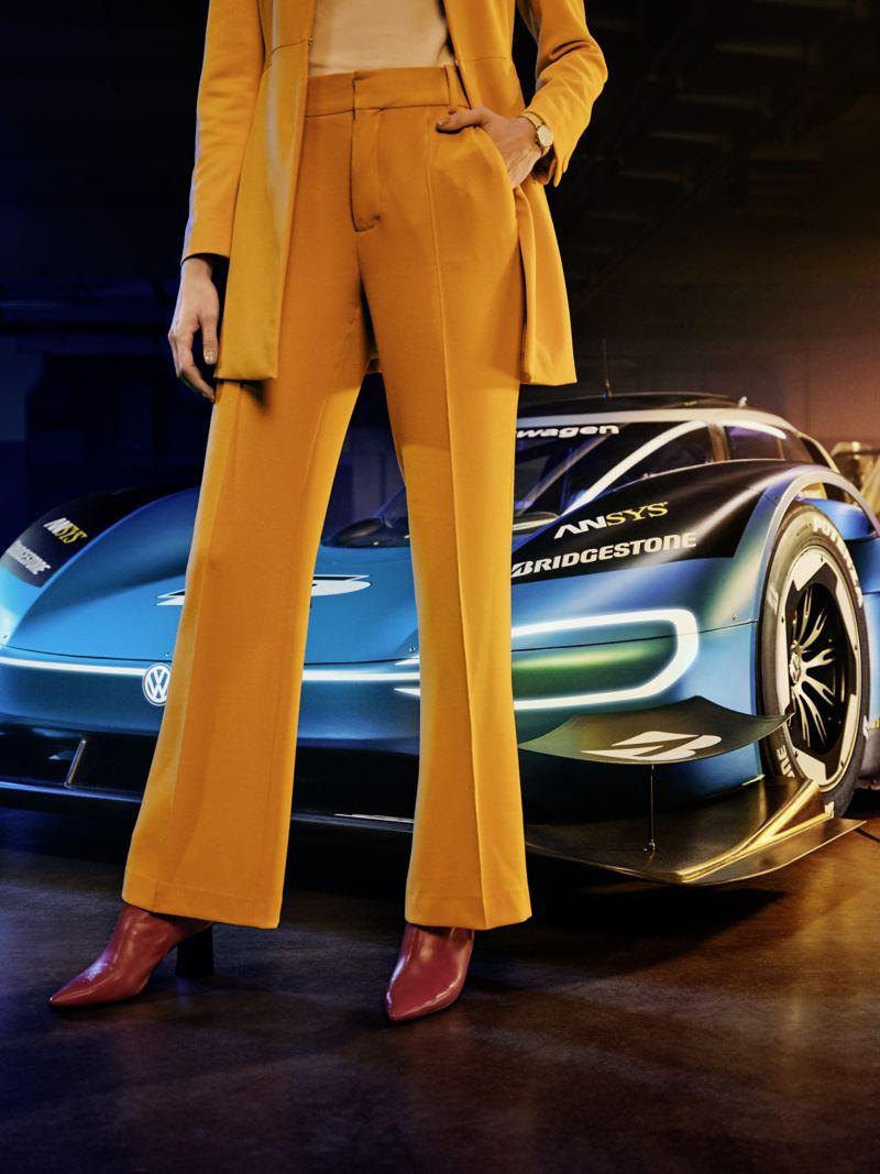 weibliches Model in Hosenanzug vor dem Volkswagen ID.R, elektrisch angetriebener Rennwagen, Lagerhalle