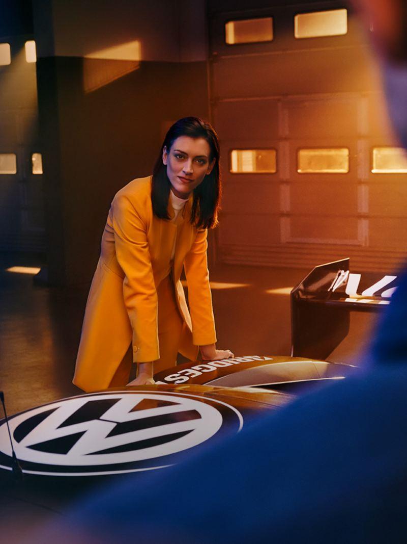 En kvinne lener seg over Volkswagen ID.R racerbil