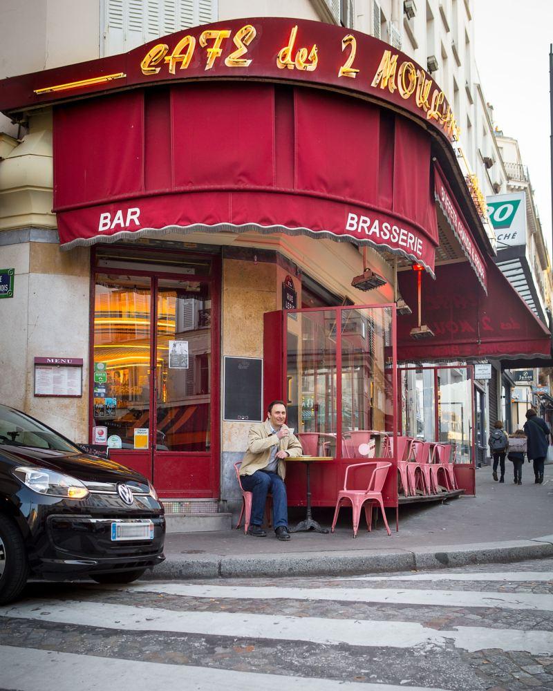 Alexandre Marie sitzt vor einem Café, sein e-up! ist neben ihm geparkt