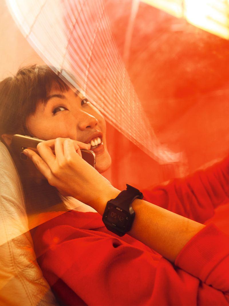Frau telefoniert auf einem Lounge Sessel mit ihrem Smartphone