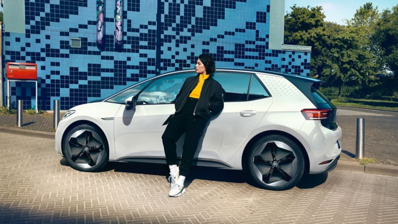 Μια νεαρή γυναίκα ακουμπά στην πόρτα του οδηγού του VW ID.3 1ST