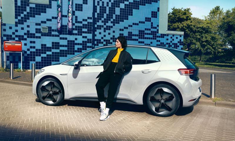 Une femme se penche sur la VW ID.3 garée au bord de la rue