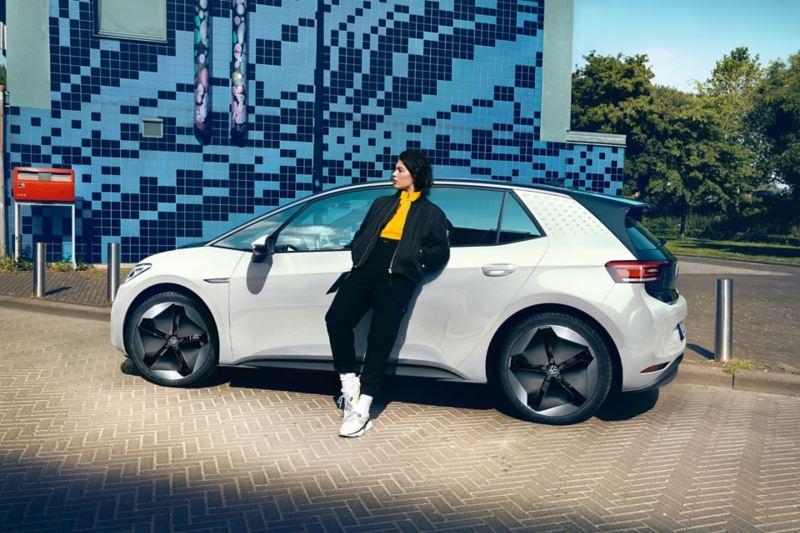 ragazza che aspetta appoggiata alla porta lato guida di VW ID.3