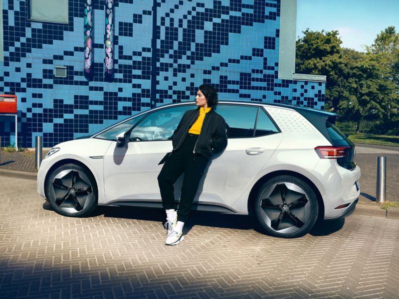 En kvinne lener seg mot en VW ID.3 som står parkert i veikanten