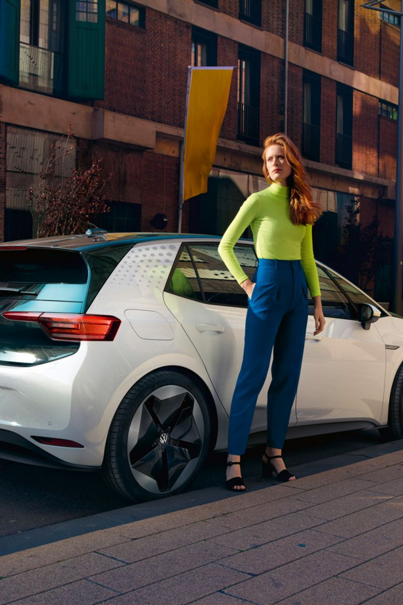 VW ID.3 von schräg hinten, eine junge Frau steht am Heck