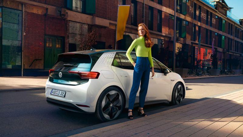 Kvinna står framför elbilen Volkswagen ID.3