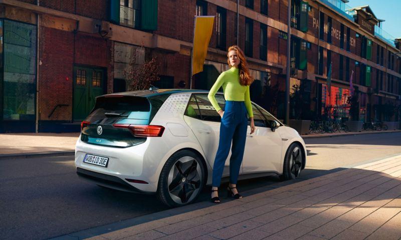 La VW ID.3 en vue oblique de derrière, une jeune femme se tient debout à l'arrière