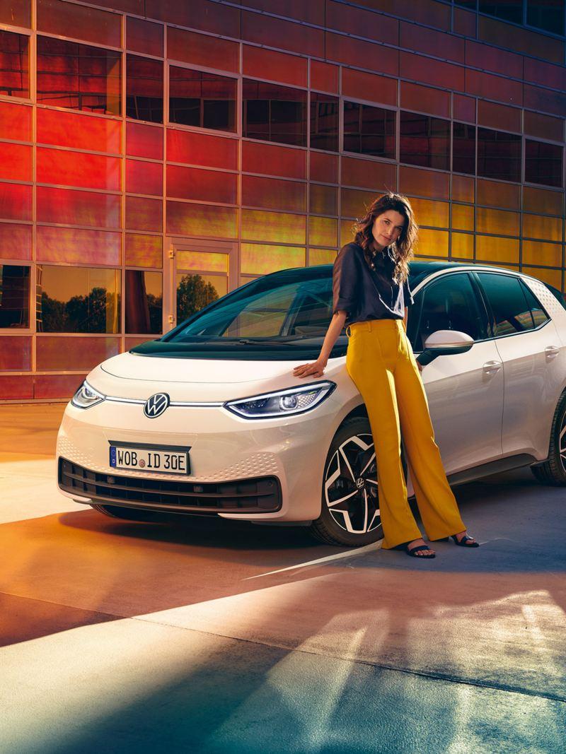Eine Frau lehnt an ihrem Volkswagen ID.3