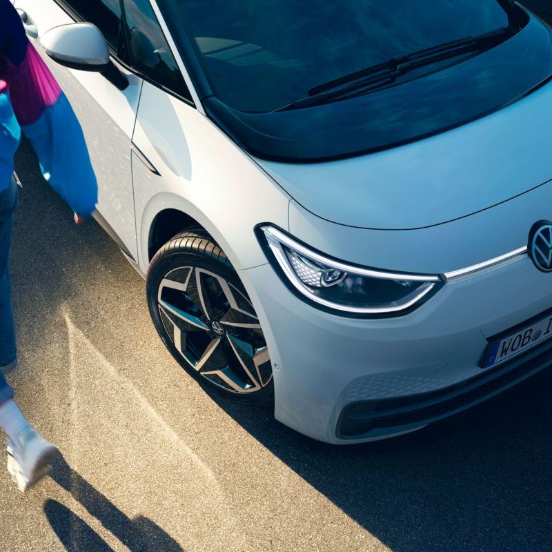 Uma mulher jovem está encostada à porta do condutor do carro elétrico VW ID.3 1ST.