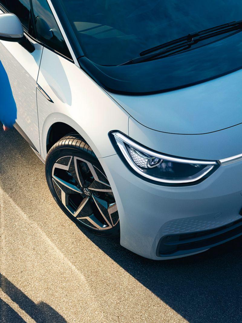 nuevo ID.3 de Volkswagen con los faros encendidos junto a un chico avanzando