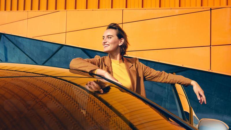 Una donna sorridente scende dalla VW ID.3