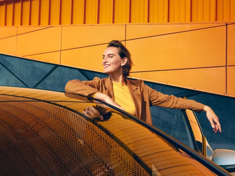 Uma mulher sorridente sai do VW ID.3