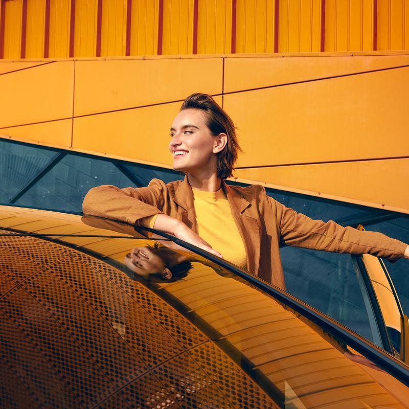 Nainen seisoo iloisena Volkswagen henkilöauton vierellä