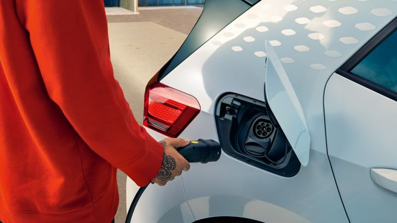 Woman plugging a charging cable into a Volkswagen