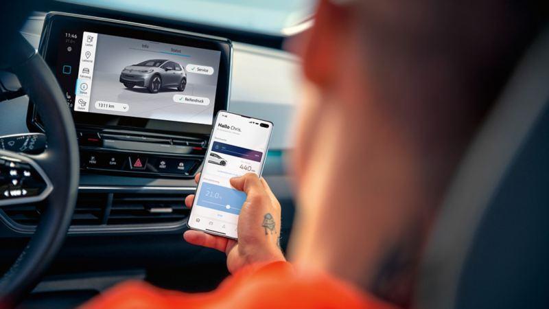 Ein junger Mann auf dem Fahrersitz des ID.3 schaut auf das Telefon in seiner Hand