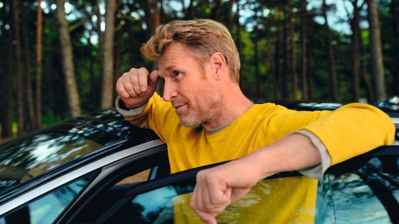 Mann in gelbem Pullover lehnt an der geöffneten Autotür