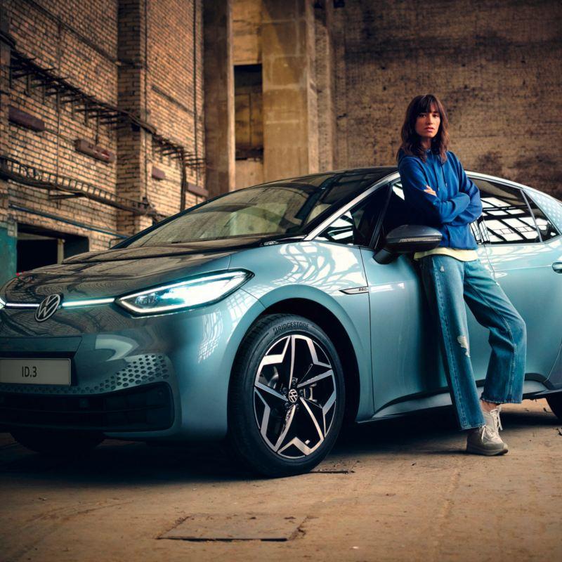 Una giovane donna si appoggia alla portiera lato guida della VW ID3 auto elettrica