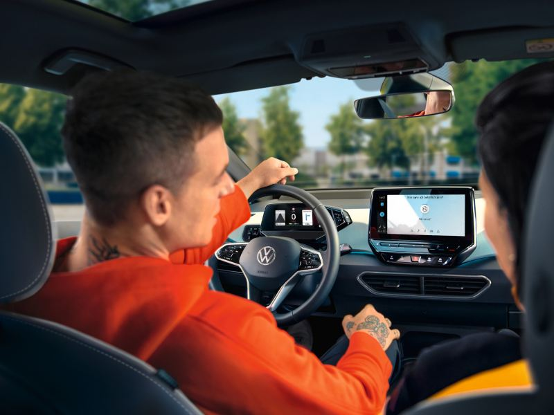 Des personnes assises sur les sièges avant de la VW ID.3 regardent l'écran de la radio