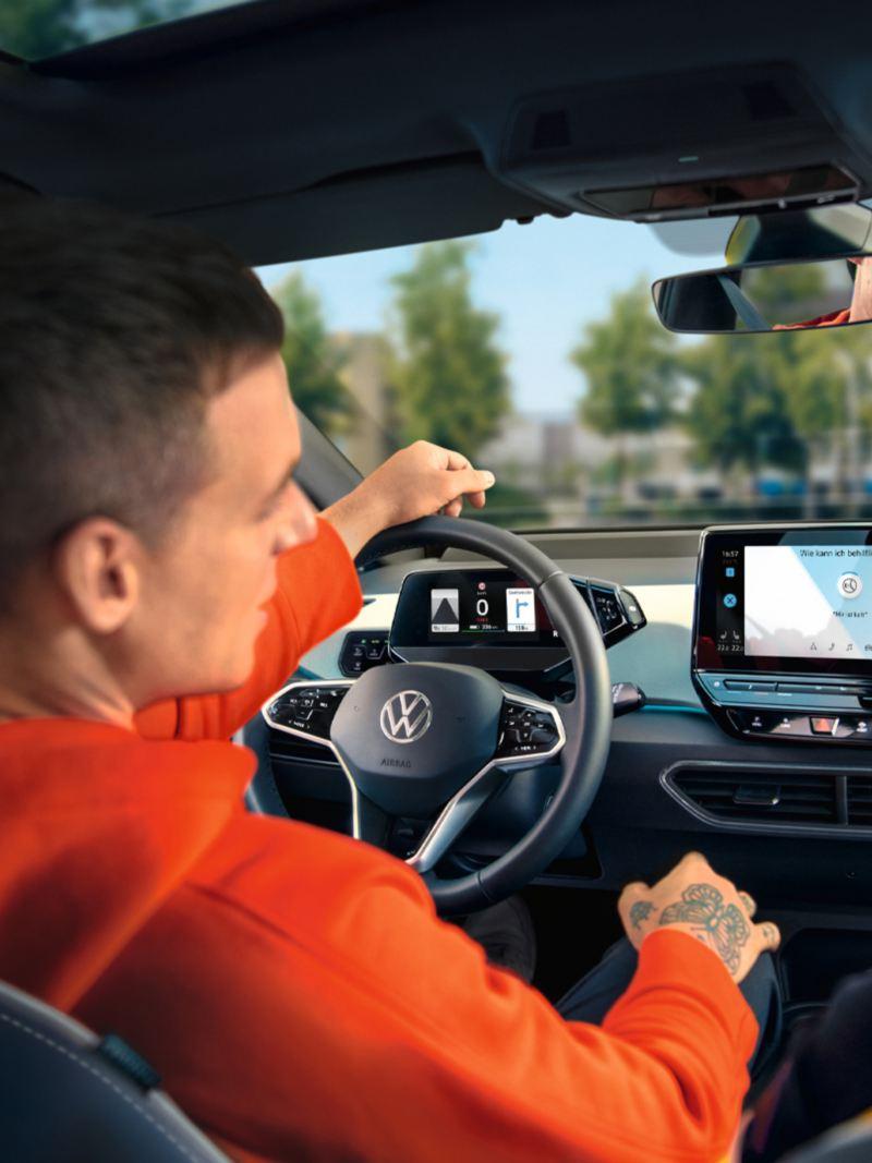 Personen auf den Vordersitzen im VW ID.3 schauen sich das Radiodisplay an