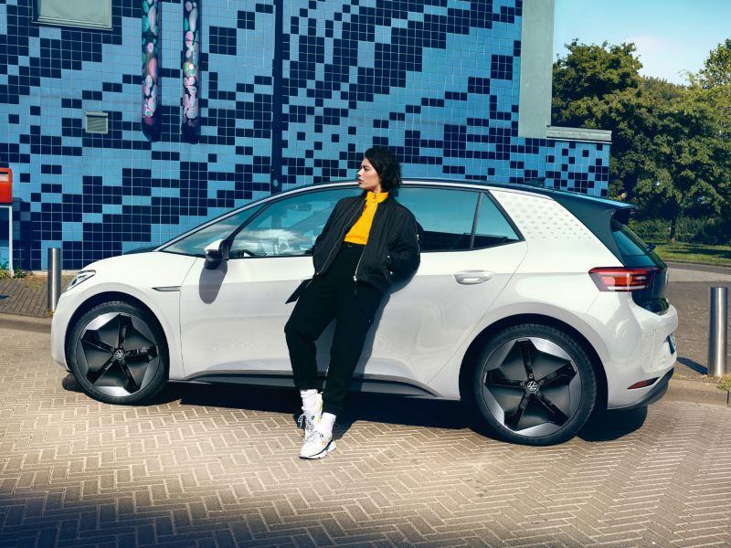 Eine junge Frau lehnt an der Seite des VW ID.3