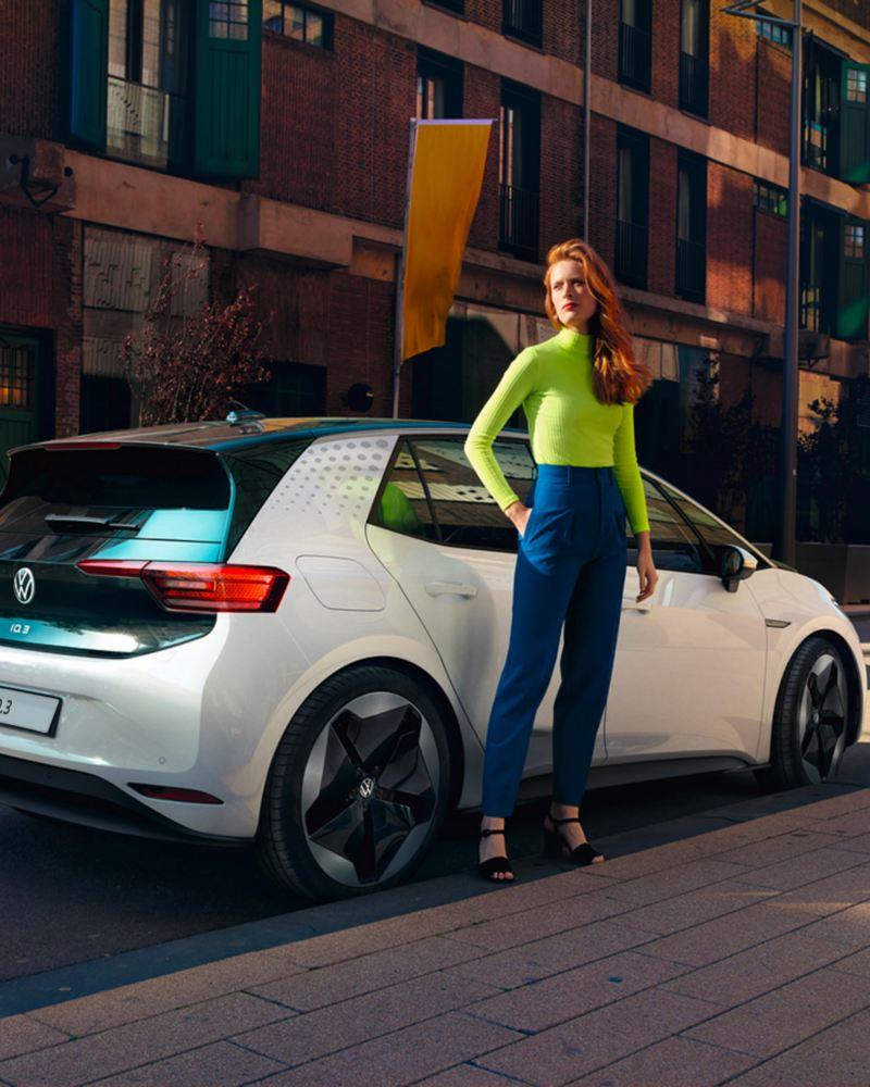 ragazza sul marciapiede a fianco di Volkswagen ID.3 auto elettrica
