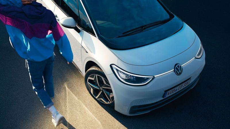 VW ID.3 Schrägansicht von vorn, Lackierung Gletscherweiß Metallic/Schwarz, Mann geht vorbei