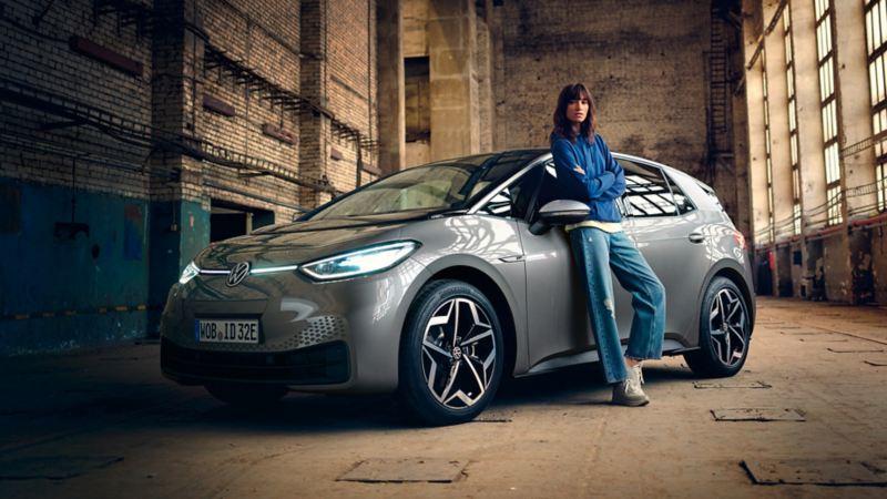 Młoda kobieta opiera się o lewe drzwi VW ID.3 1ST