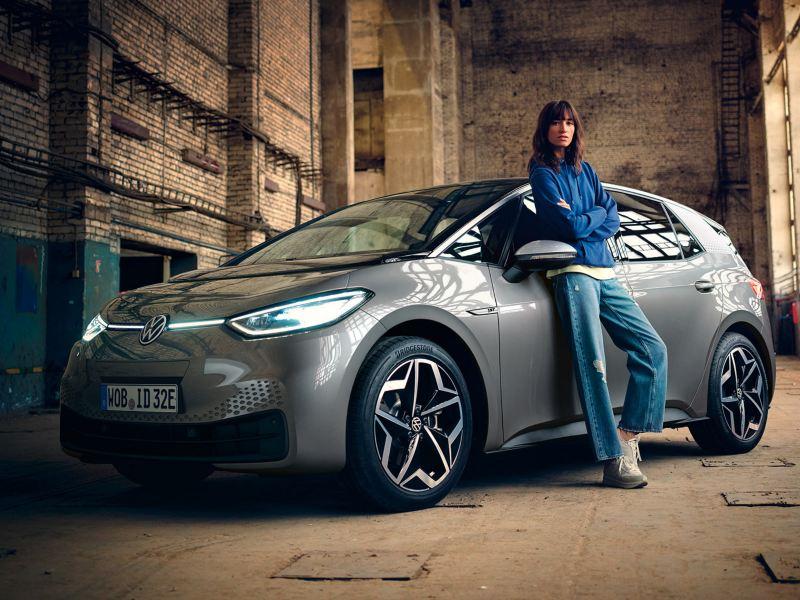 Junge Frau lehnt am VW ID.3 1st in einer alten Lagerhalle