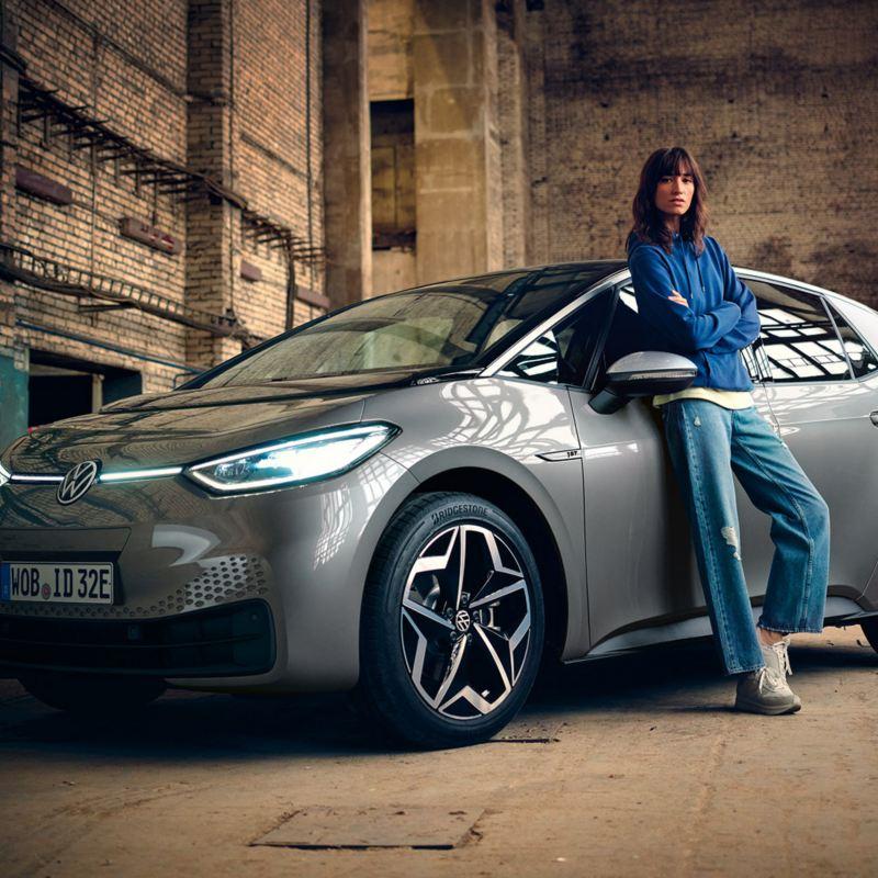 Eine junge Frau lehnt an der Fahrertür des VW ID.3 1ST