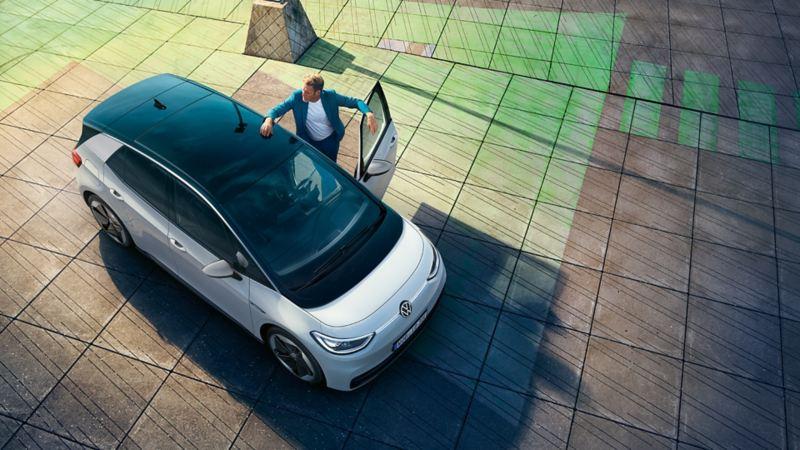Blick von oben auf den VW ID.3, Mann steht in der geöffneten Fahrertür