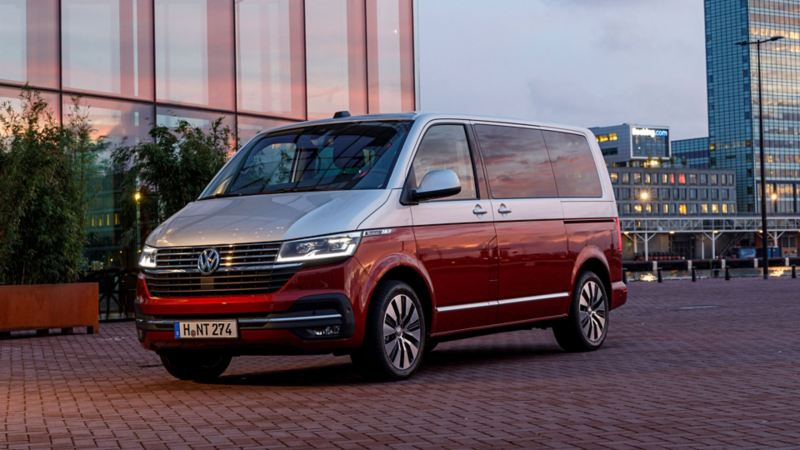 Vista 3/4 frontale del nuovo Bulli 6.1 Volkswagen parcheggiato davanti a un palazzo.
