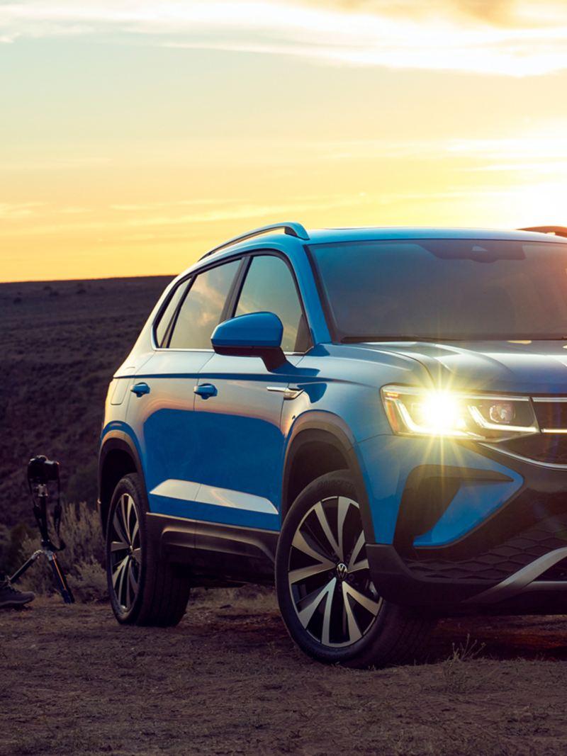 Vue de face d'un Taos bleu à côté d'une tente dans le désert au coucher du soleil. Ses phares sont allumés alors que le soleil se couche.